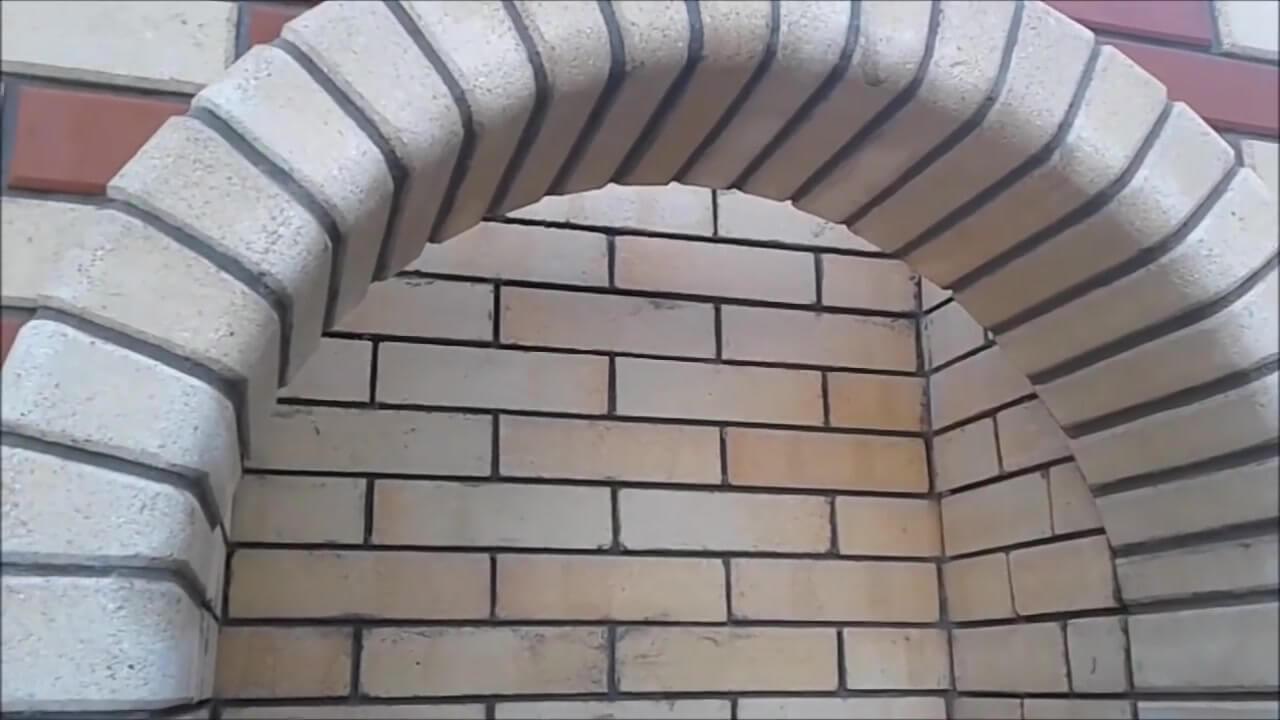 Убираем лишний раствор между кирпичами арки