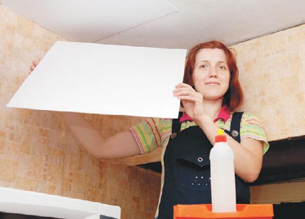 У девушки в руках потолочная плитка