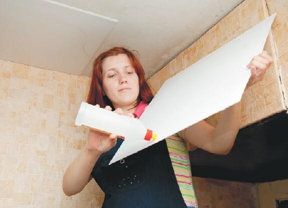 Девушка показывает: Клей можно наносить на внутреннюю поверхность плитки
